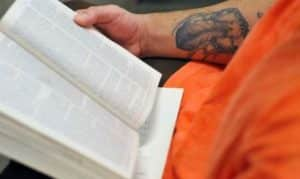 prisoner in an orange jump suit reading a book