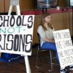 A young woman representing the Harvard Association for Prison Education sits at a protest against solitary confinement in the U.S.